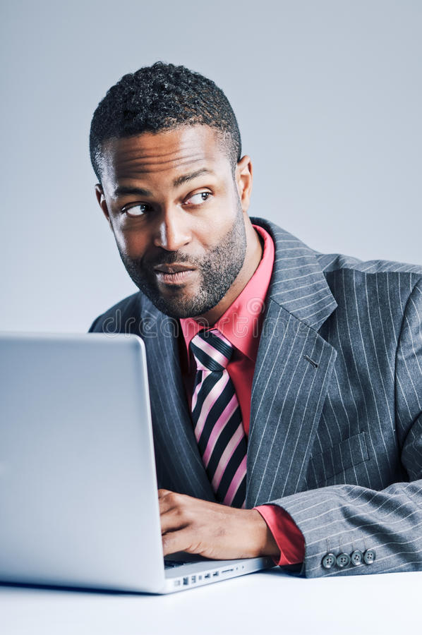 Jonge Afrikaanse Amerikaanse Laptop van Zakenmanbeing sneaky on royalty-vrije stock afbeeldingen