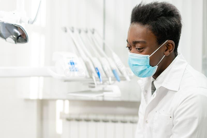 Jonge Afrikaanse Amerikaanse mannelijke artsentandarts in een medisch masker Geneeskunde, gezondheid, de stomatologieconcept tand royalty-vrije stock foto's