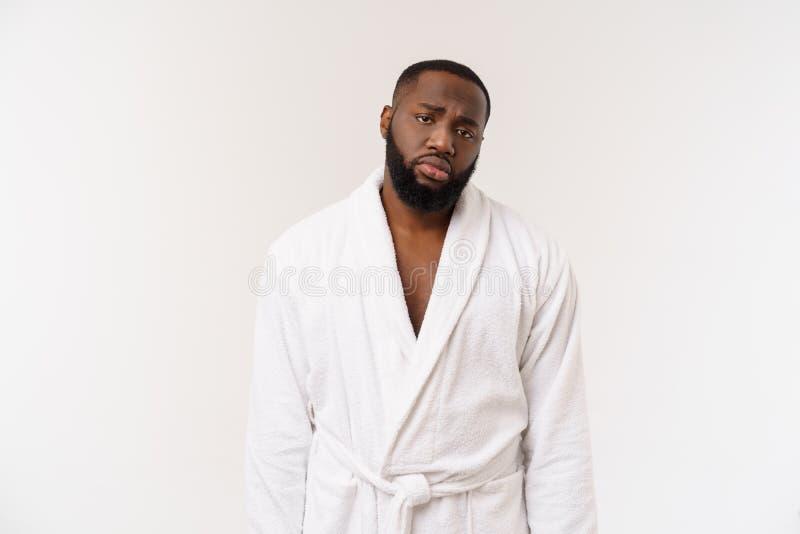 Jonge Afrikaanse Amerikaanse mens die badjas over geïsoleerde witte achtergrond dragen die vermoeid en bored het kijken denken me stock foto's