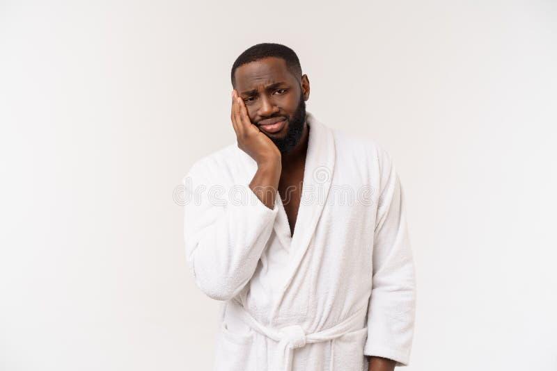 Jonge Afrikaanse Amerikaanse mens die badjas over geïsoleerde witte achtergrond dragen die vermoeid en bored het kijken denken me royalty-vrije stock afbeelding