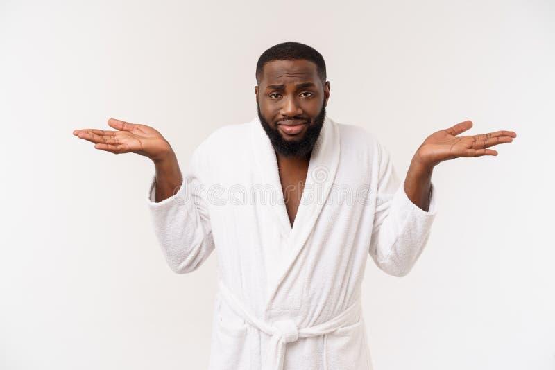 Jonge Afrikaanse Amerikaanse mens die badjas over geïsoleerde witte achtergrond dragen die vermoeid en bored het kijken denken me royalty-vrije stock fotografie