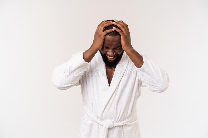 Jonge Afrikaanse Amerikaanse mens die badjas over geïsoleerde witte achtergrond dragen die vermoeid en bored het kijken denken me royalty-vrije stock afbeeldingen