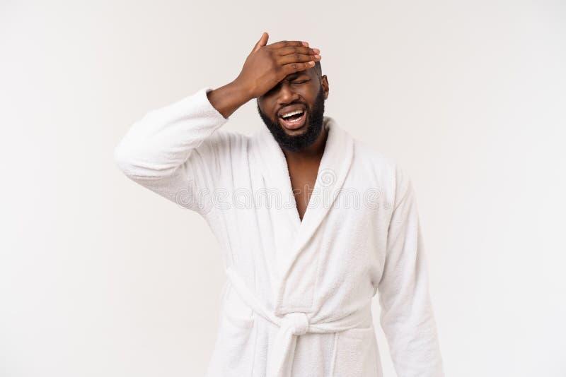 Jonge Afrikaanse Amerikaanse mens die badjas over geïsoleerde witte achtergrond dragen die vermoeid en bored het kijken denken me stock fotografie