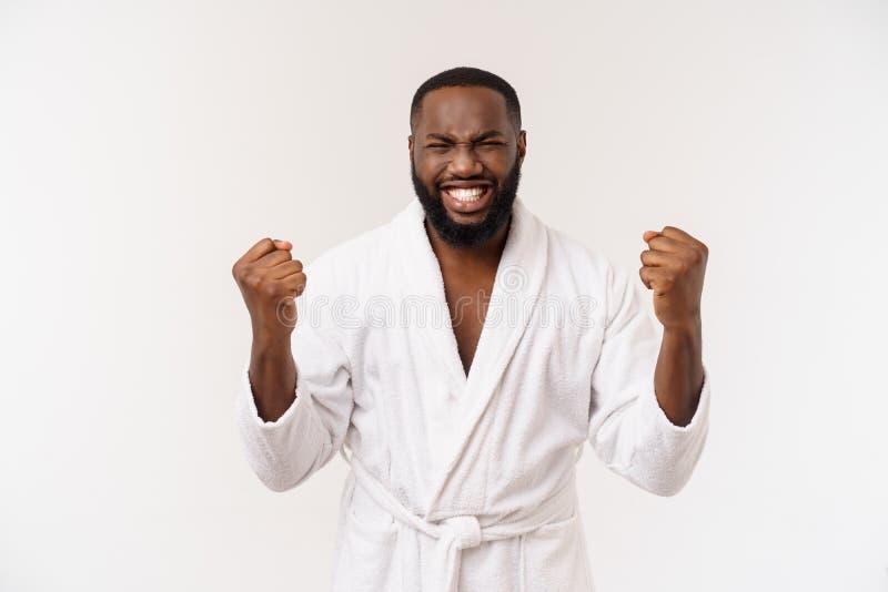 Jonge Afrikaanse Amerikaanse mens die in badjas trots en het vieren zeer opgewekte overwinning en succes gillen, het toejuichen stock afbeelding