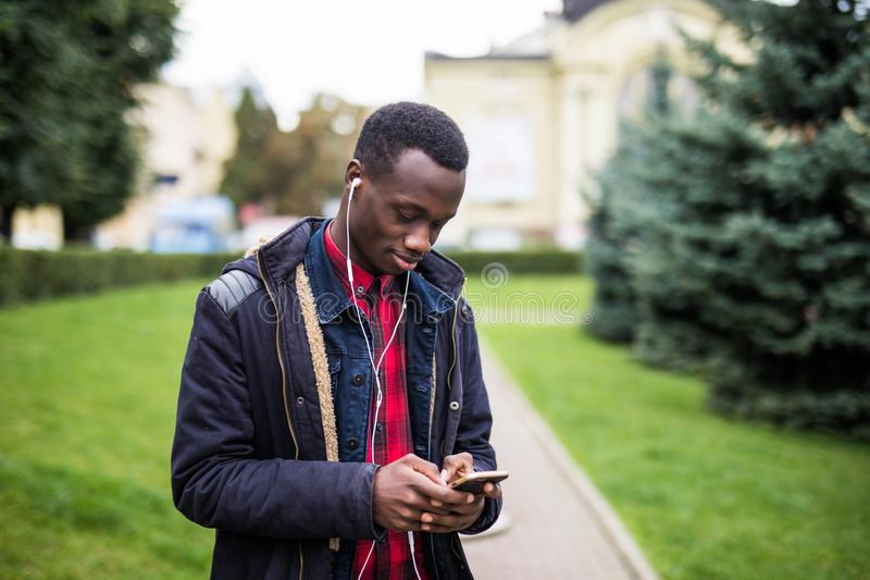Jonge Afrikaanse Amerikaanse mens in hoofdtelefoon die bij zonnige stad lopen en aan muziek op zijn slimme telefoon genieten van  stock foto