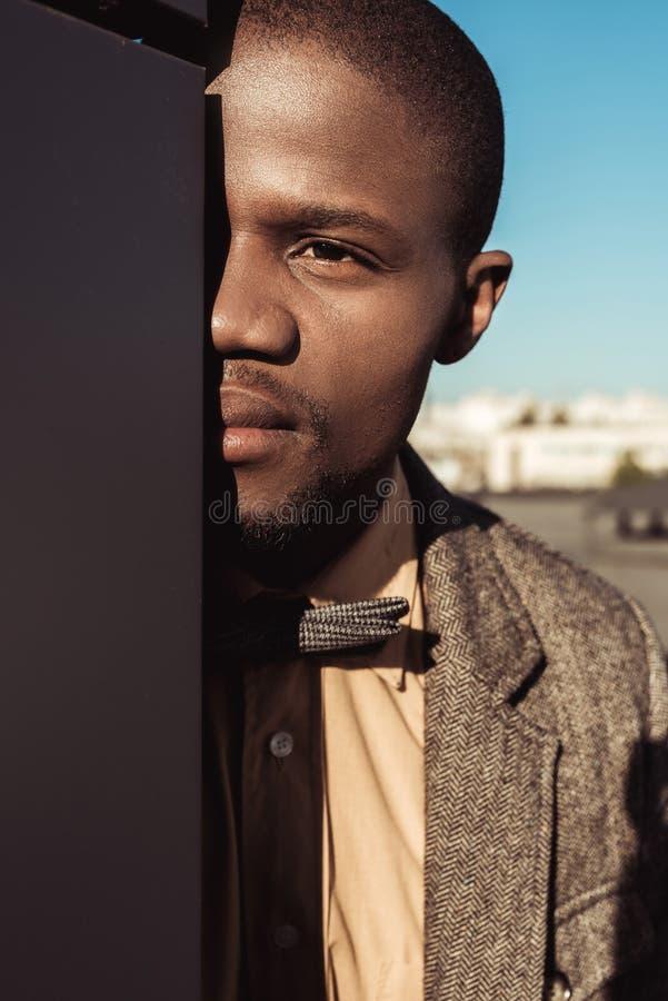 Jonge Afrikaanse Amerikaanse mens in kostuum en bowtie de verbergende helft van zijn gezicht erachter royalty-vrije stock foto