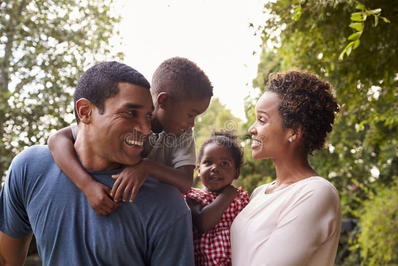Jonge Afrikaanse Amerikaanse ouders die kinderen in tuin vervoeren stock foto's