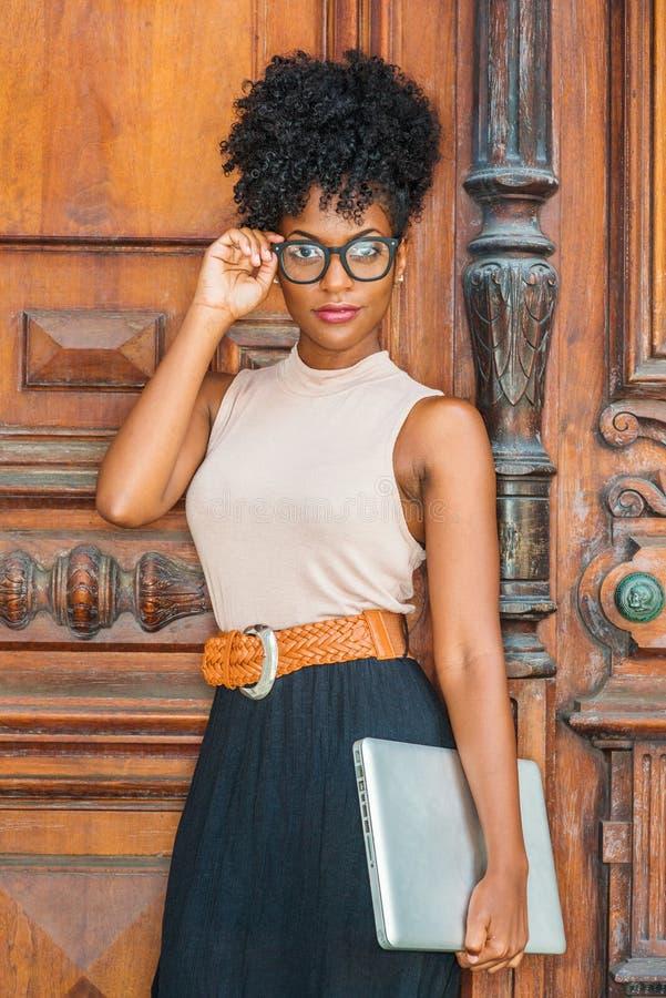 Jonge Afrikaanse Amerikaanse Student met afrokapsel, oogglazen, die sleeveless lichte kleuren hoogste, zwarte rok, riem dragen, stock afbeeldingen