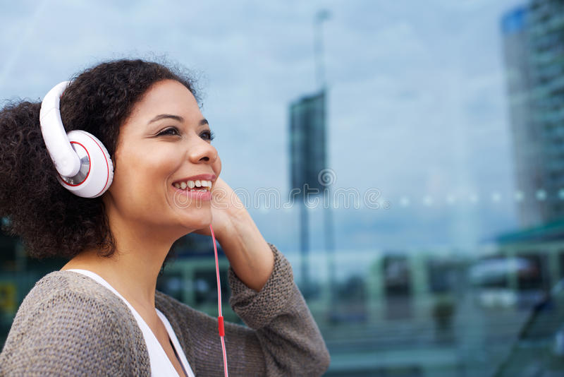 Jonge Afrikaanse Amerikaanse vrouw die aan muziek op hoofdtelefoons luisteren stock foto