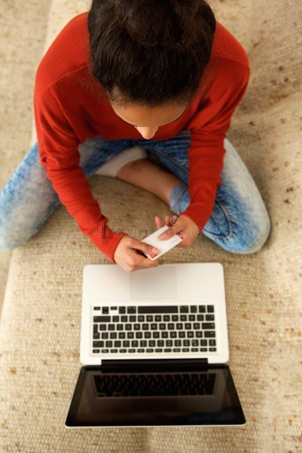 Jonge Afrikaanse Amerikaanse vrouw die creditcard met laptop gebruiken royalty-vrije stock afbeeldingen