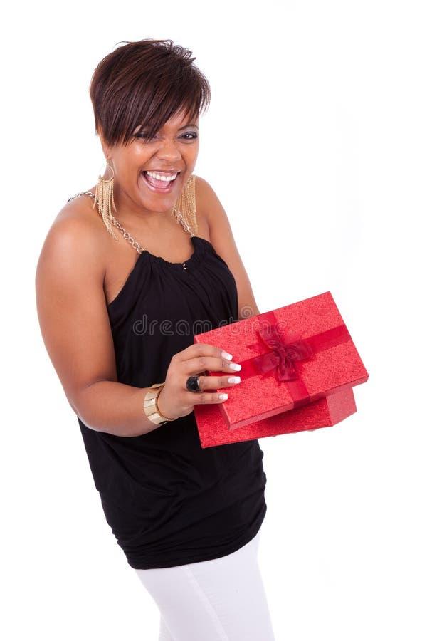Jonge Afrikaanse Amerikaanse vrouw die een gift openen royalty-vrije stock foto's