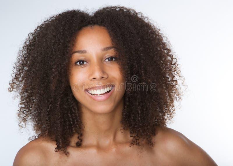 Jonge Afrikaanse Amerikaanse vrouw die met krullend haar glimlachen stock afbeelding