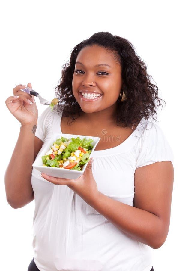 Jonge Afrikaanse Amerikaanse vrouw die salade eet stock foto's