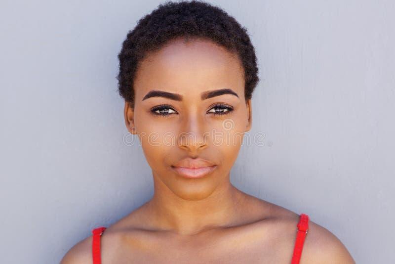 Jonge Afrikaanse Amerikaanse vrouw tegen het grijze muur staren stock foto
