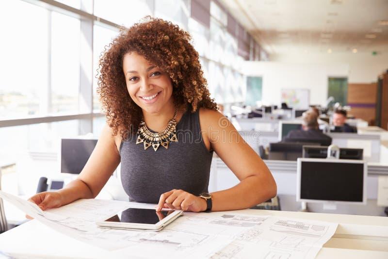 Jonge Afrikaanse Amerikaanse vrouwelijke architect die in een bureau werken royalty-vrije stock afbeeldingen