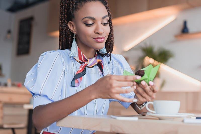 Jonge Afrikaanse Amerikaanse vrouwenzitting bij de lijst in koffie winkel en het eten van a stock foto's