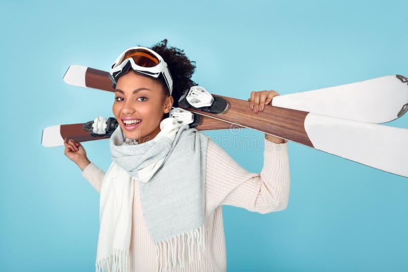 Jonge Afrikaanse die vrouw bij het blauwe de wintersport van de muurstudio ski?en wordt geïsoleerd die zich met skis zijaanzicht  royalty-vrije stock afbeeldingen