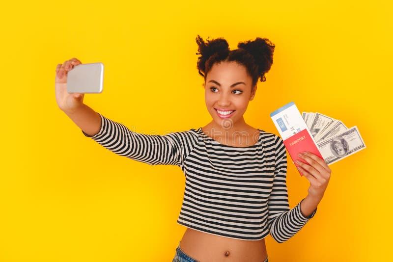 Jonge Afrikaanse die vrouw bij het gele de reiziger van de de tienerstijl van de muurstudio nemen wordt geïsoleerd selfie stock afbeeldingen