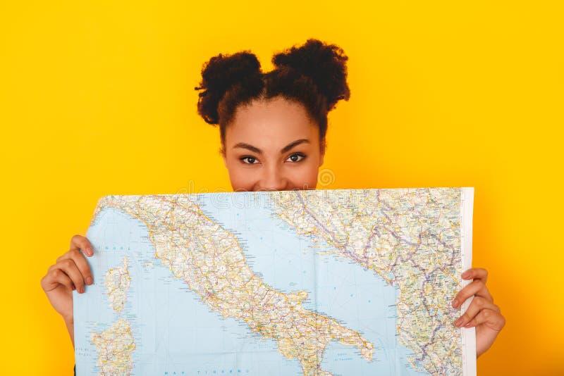 Jonge Afrikaanse die vrouw bij het gele de reiziger van de de tienerstijl van de muurstudio verbergen achter kaart wordt geïsolee stock foto's