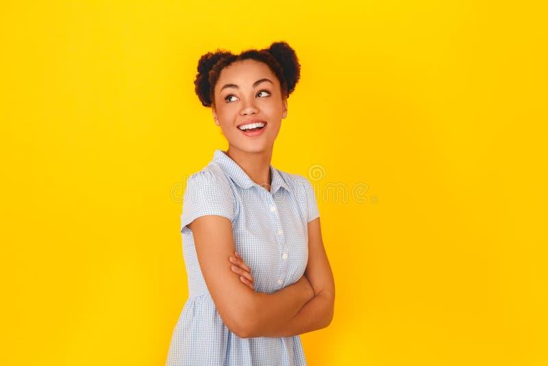 Jonge Afrikaanse die vrouw bij het gele het meisjesstijl van de muurstudio leuke dromen wordt geïsoleerd stock foto