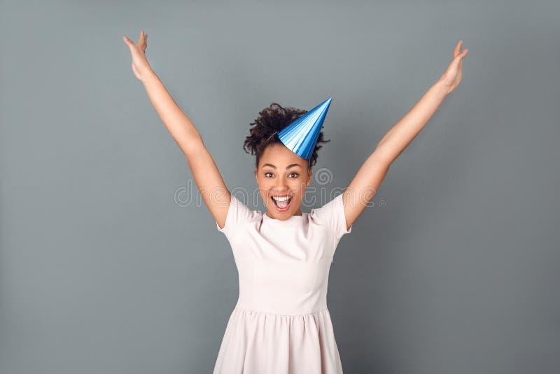 Jonge Afrikaanse die vrouw bij het grijze de vieringsconcept van de muurstudio springen wordt geïsoleerd stock afbeelding