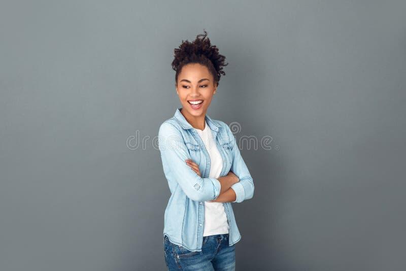 Jonge Afrikaanse die vrouw bij het grijze toevallige dagelijkse de levensstijl van de muurstudio lachen wordt geïsoleerd royalty-vrije stock fotografie