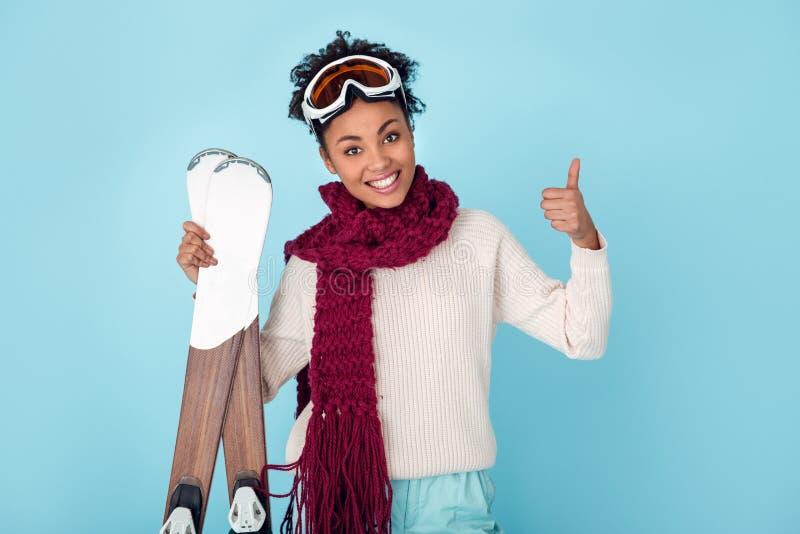 Jonge Afrikaanse die vrouw op blauwe de wintersport van de muurstudio het ski?en duim omhoog wordt geïsoleerd royalty-vrije stock afbeeldingen