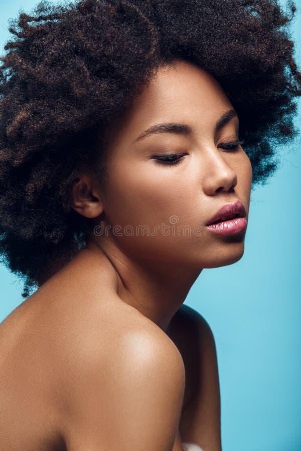 Jonge Afrikaanse die vrouw op de blauwe manier van de muurstudio photoshoot wordt geïsoleerd royalty-vrije stock afbeelding