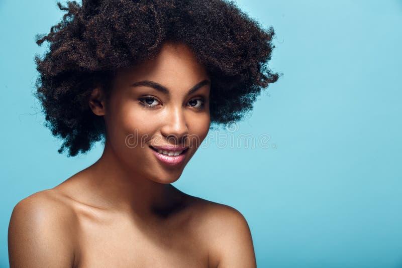 Jonge Afrikaanse die vrouw op de blauwe manier die van de muurstudio photoshoot wordt geïsoleerd glimlachen stock fotografie
