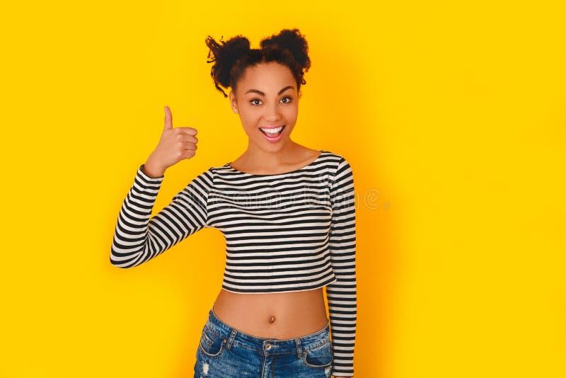 Jonge Afrikaanse die vrouw op de gele duim van de de tienerstijl van de muurstudio omhoog wordt geïsoleerd royalty-vrije stock foto's