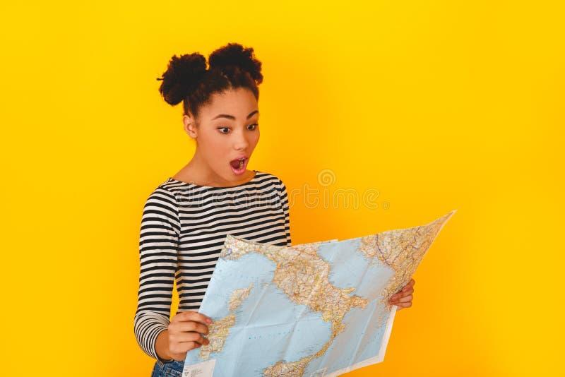Jonge Afrikaanse die vrouw op de gele reiziger wordt geïsoleerd die van de de tienerstijl van de muurstudio geschokte kaart bekij stock foto
