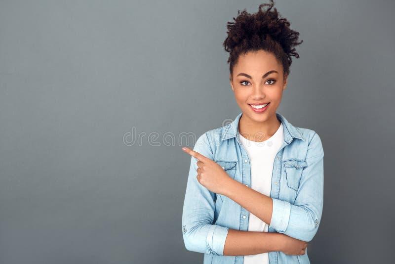 Jonge Afrikaanse die vrouw op de grijze toevallige dagelijkse levensstijl van de muurstudio copyspace wordt geïsoleerd royalty-vrije stock fotografie