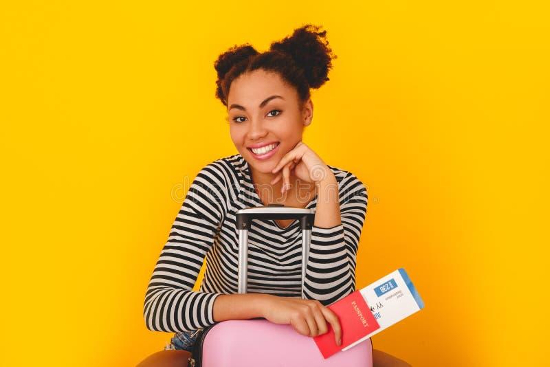 Jonge Afrikaanse die vrouw op gele van de de tienerstijl van de muurstudio de reizigerszitting wordt geïsoleerd op koffer stock afbeelding