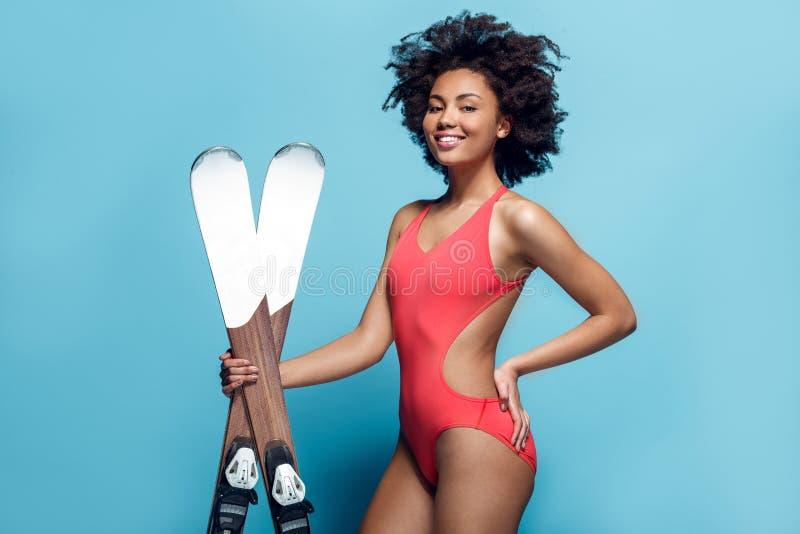 Jonge Afrikaanse die vrouw in zwempak bij het blauwe muurstudio het ski?en stellen wordt geïsoleerd stock fotografie