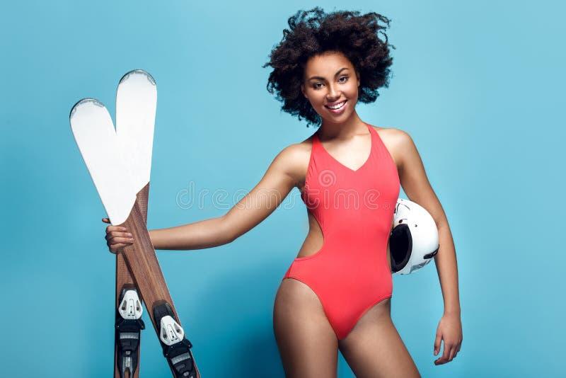 Jonge Afrikaanse die vrouw in zwempak op blauwe muurstudio het ski?en holdingshelm wordt geïsoleerd royalty-vrije stock foto