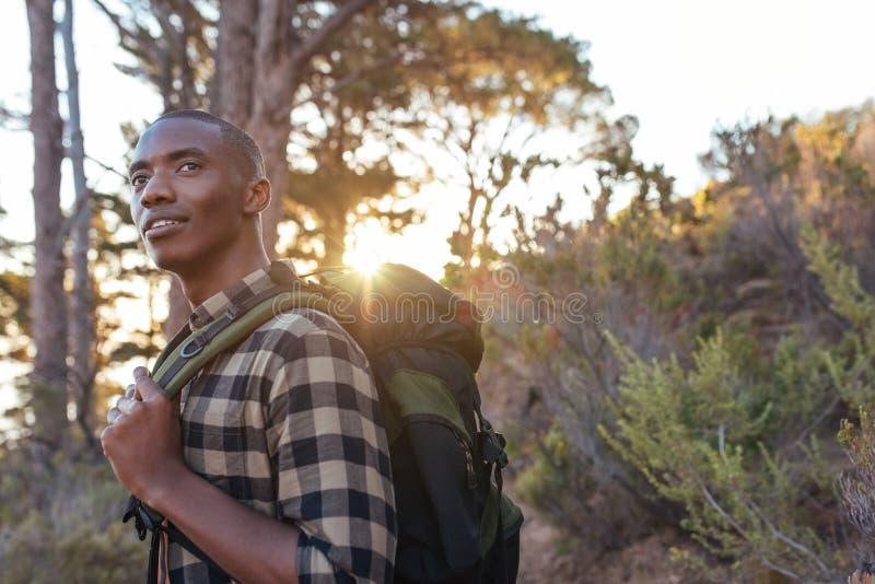 Jonge Afrikaanse mens die alleen in de wildernis bij schemer wandelen royalty-vrije stock foto's