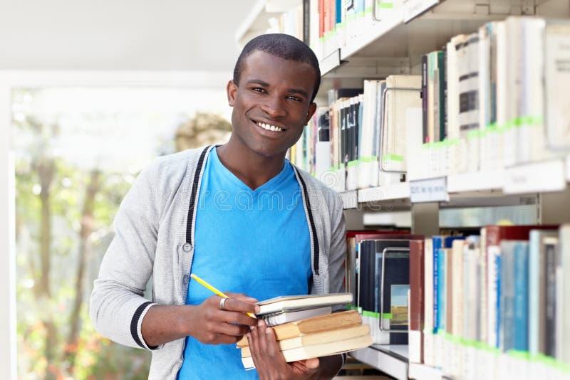 Jonge Afrikaanse mens die in bibliotheek glimlacht royalty-vrije stock afbeelding
