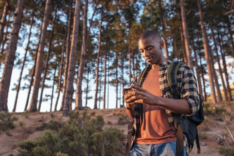 Jonge Afrikaanse mens die gps met behulp van terwijl wandeling in een bos royalty-vrije stock fotografie