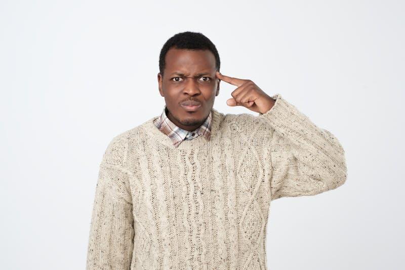 Jonge Afrikaanse mens die met zijn vinger op hoofd richten Hij is niet tevreden met situatie royalty-vrije stock foto