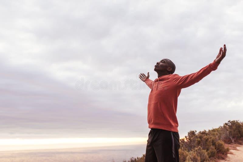 Jonge Afrikaanse mens die zich op een sleep buiten het omhelzen van aard bevinden stock fotografie