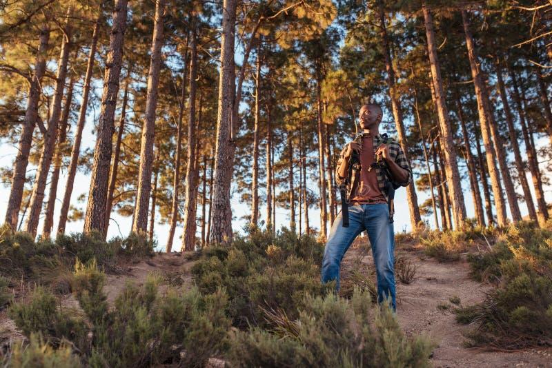 Jonge Afrikaanse mens die zich op een sleep in het bos bevinden stock foto