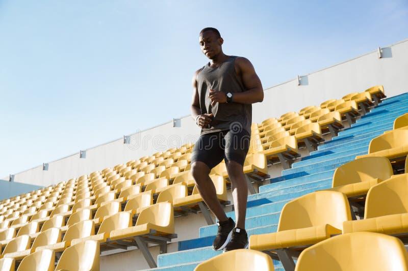 Jonge Afrikaanse mensenagent in sportkleren die beneden a in werking stellen royalty-vrije stock fotografie
