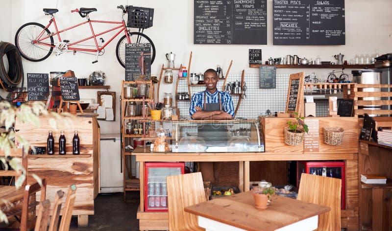 Jonge Afrikaanse ondernemer die zich achter de teller van zijn koffie bevinden royalty-vrije stock fotografie