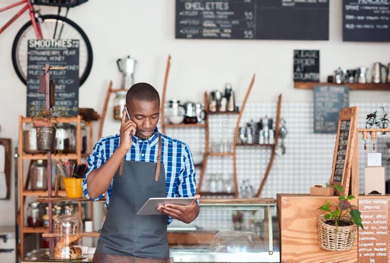 Jonge Afrikaanse ondernemer hard bij het werk in zijn in koffie stock fotografie