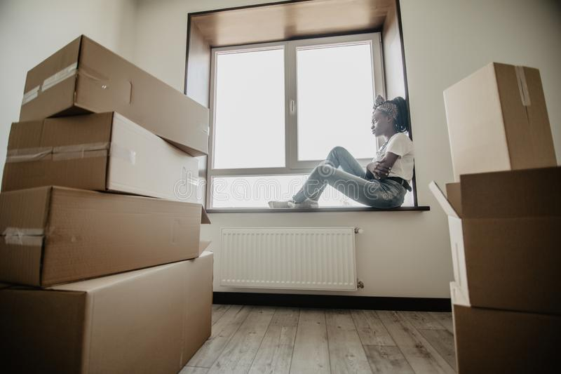 Jonge Afrikaanse vrouw die binnenshuis het zitten op de vensterbank bewegen Verhuizingsconcept royalty-vrije stock fotografie