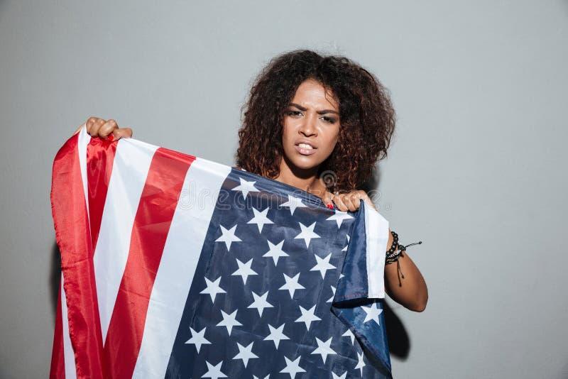 Jonge Afrikaanse vrouw die de vlag van de V.S. proberen te verscheuren stock foto's