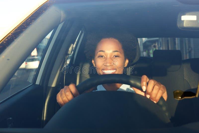 Jonge Afrikaanse vrouw die een auto en het glimlachen drijven stock afbeelding