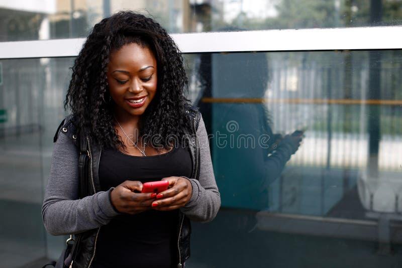 Jonge Afrikaanse vrouw die een tekstbericht lezen stock foto's