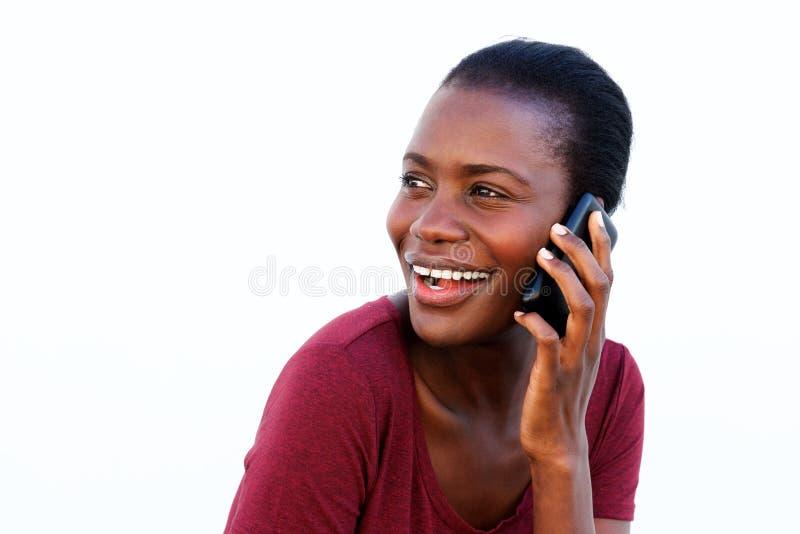 Jonge Afrikaanse vrouw die een telefoongesprek maken kijkend over schouder en glimlachend op witte achtergrond stock afbeeldingen