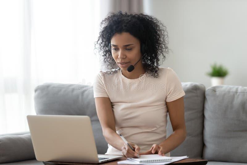 Jonge Afrikaanse vrouw die hoofdtelefoon draagt die laptop bekijkt die nota's maakt stock afbeeldingen